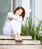 A cheerful woman sitting on steps Royalty Free Stock Photo