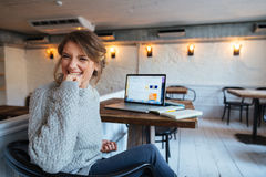 Cheerful woman sitting at the table in cafe Royalty Free Stock Photography