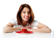 Cheerful woman sitting at the table with fresh strawberry cake Stock Image