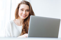 Cheerful woman sitting at the table with laptop Stock Photography