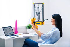 Cheerful woman sitting at the table. Magic invention. Pleasant beautiful smiling delighted woman sitting at the table and holding model printed on the 3dprinter royalty free stock photos