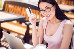 Cheerful woman sitting at the table. Positivity in mind. Cheerful beautiful smiling young woman holding credit card and sitting at the table while expressing royalty free stock image