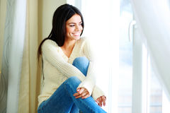 Cheerful woman sitting on a window-sill and looking outside Royalty Free Stock Photos