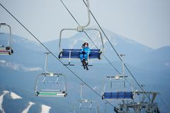 Cheerful woman skier in blue ski suit riding up to the top of the mountain on a cable ski lift with skies Royalty Free Stock Photos