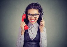 Cheerful woman with smartphone and retro telephone royalty free stock images