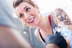 Cheerful woman smiling with confidence in a modern tattoo studio. Portrait of a cheerful fashionable women smiling while looking at the tattoo artist with royalty free stock image