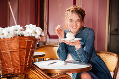 Cheerful woman smiling and eating cupcake in outdoor cafe royalty free stock images