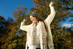 Cheerful woman smiling outdoors on a sunny fall day with arms outstretched Stock Images