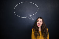 Cheerful woman smiling over blackboard with empty speech bubble Royalty Free Stock Photography