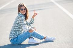 Cheerful woman smiling sitting on the road. Young smiling woman outdoors portrait,Young beautiful woman brunette with long thick hair and black sun glasses Stock Image