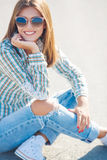 Cheerful woman smiling sitting on the road. Young smiling woman outdoors portrait,Young beautiful woman brunette with long thick hair and black sun glasses Royalty Free Stock Images