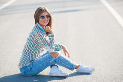Cheerful woman smiling sitting on the road. Young smiling woman outdoors portrait,Young beautiful woman brunette with long thick hair and black sun glasses Stock Photos