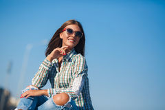 Cheerful woman smiling sitting on the road. Young smiling woman outdoors portrait,Young beautiful woman brunette with long thick hair and black sun glasses Royalty Free Stock Photos
