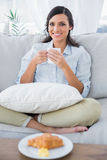Cheerful woman on sofa drinking coffee and having croissant Royalty Free Stock Photography