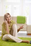 Woman talking on cell at home Royalty Free Stock Photos