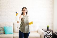 Cheerful woman spraying disinfectant in house. Beautiful young woman is using a spray while cleaning house Royalty Free Stock Photos