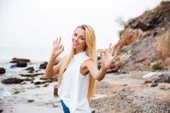Cheerful woman standing on the beach and showing ok sign. Cheerful charming young woman standing on the beach and showing ok sign Royalty Free Stock Images