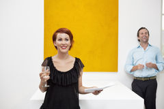 Cheerful woman standing in front of yellow painting with man in background Royalty Free Stock Photo