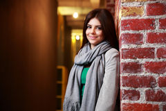 Cheerful woman standing near the brick wall Royalty Free Stock Photos
