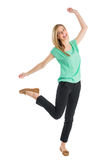 Cheerful Woman Standing On One Leg With Hands Raised Royalty Free Stock Photos