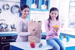 Cheerful woman standing with paper bag and her daughter sitting with yellow pepper stock image