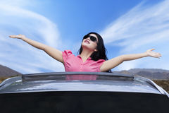 Cheerful woman standing on the sunroof. Picture of cheerful young woman wearing sunglasses and raised hands on the sunroof of the luxury car Royalty Free Stock Images
