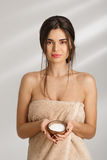 Cheerful woman standing in towel, holding body scrub, looking straight. Young cheerful woman standing in towel, holding body scrub, looking straight with Stock Photos