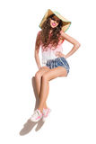 Cheerful Woman In Straw Hat. Smiling sexy young woman in straw hat, pink top, jeans shorts and pink sneakers sitting on the top of white banner. Full length Stock Image