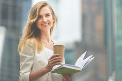 Cheerful woman in the street drinking coffee stock image