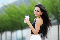 Cheerful woman in the street drinking morning coffee in sunshine.  stock photos