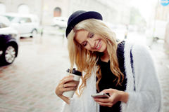Cheerful woman in the street drinking morning coffee and use her smartphone. Royalty Free Stock Photo