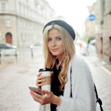 Cheerful woman in the street drinking morning coffee and use her smartphone. Royalty Free Stock Image
