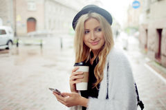 Cheerful woman in the street drinking morning coffee and use her smartphone. Stock Photography