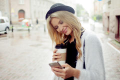 Cheerful woman in the street drinking morning coffee and use her smartphone. Royalty Free Stock Photos