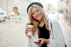 Cheerful woman in the street drinking morning coffee and use her smartphone. Royalty Free Stock Photography