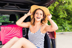 Cheerful woman on summer travel vacation sitting in a car trunk. stock photo