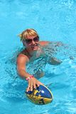 Fashionable woman with ball for rugby swimming in blue water of pool. Cheerful woman in sunglasses with ball for rugby swimming in pool. Fashionable woman with royalty free stock photography