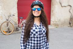 Cheerful woman with sunglasses and helmet on the background red door and bicycle stock photo