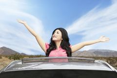 Cheerful woman on sunroof of car Stock Image