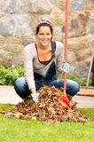 Cheerful woman sweeping leaves autumn pile backyard. Cheerful woman sweeping leaves fall pile backyard housework outdoor Royalty Free Stock Images