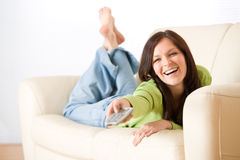 Cheerful woman switch television in living room Stock Photography