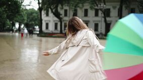 Cheerful woman taking off her umbrella to enjoy the rain in the city