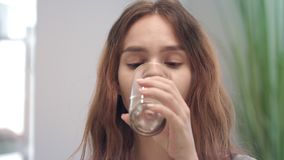 Cheerful woman taking vitamin capsule and drinking water from glass in bath room. Portrait smiling woman drinking water with medicine tablet. Woman health and stock video