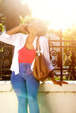 Cheerful woman talking on cell phone with bright sunlight Stock Images