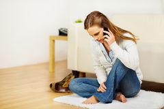 Cheerful woman talking on mobile phone at home Royalty Free Stock Photos