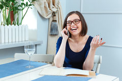 Cheerful woman talking on mobile phone and laughing in cafe Royalty Free Stock Images