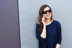 Cheerful woman talking on the phone in the street casual outfit Royalty Free Stock Photography
