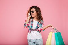 Cheerful woman talking on smartphone and holding bags isolated. Cheerful casual brunette woman talking on smartphone and holding shopping bags isolated over pink Stock Image