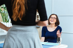 Cheerful woman talking to waitress and making order in cafe Royalty Free Stock Photos