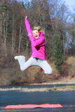 Cheerful woman teenage girl in pink tracksuit jumping outdoor. Full length of cheerful woman teenage girl in pink tracksuit jumping high outdoor. Healthy active Stock Photo